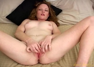 Cute naked honey on her back rubbing her clit